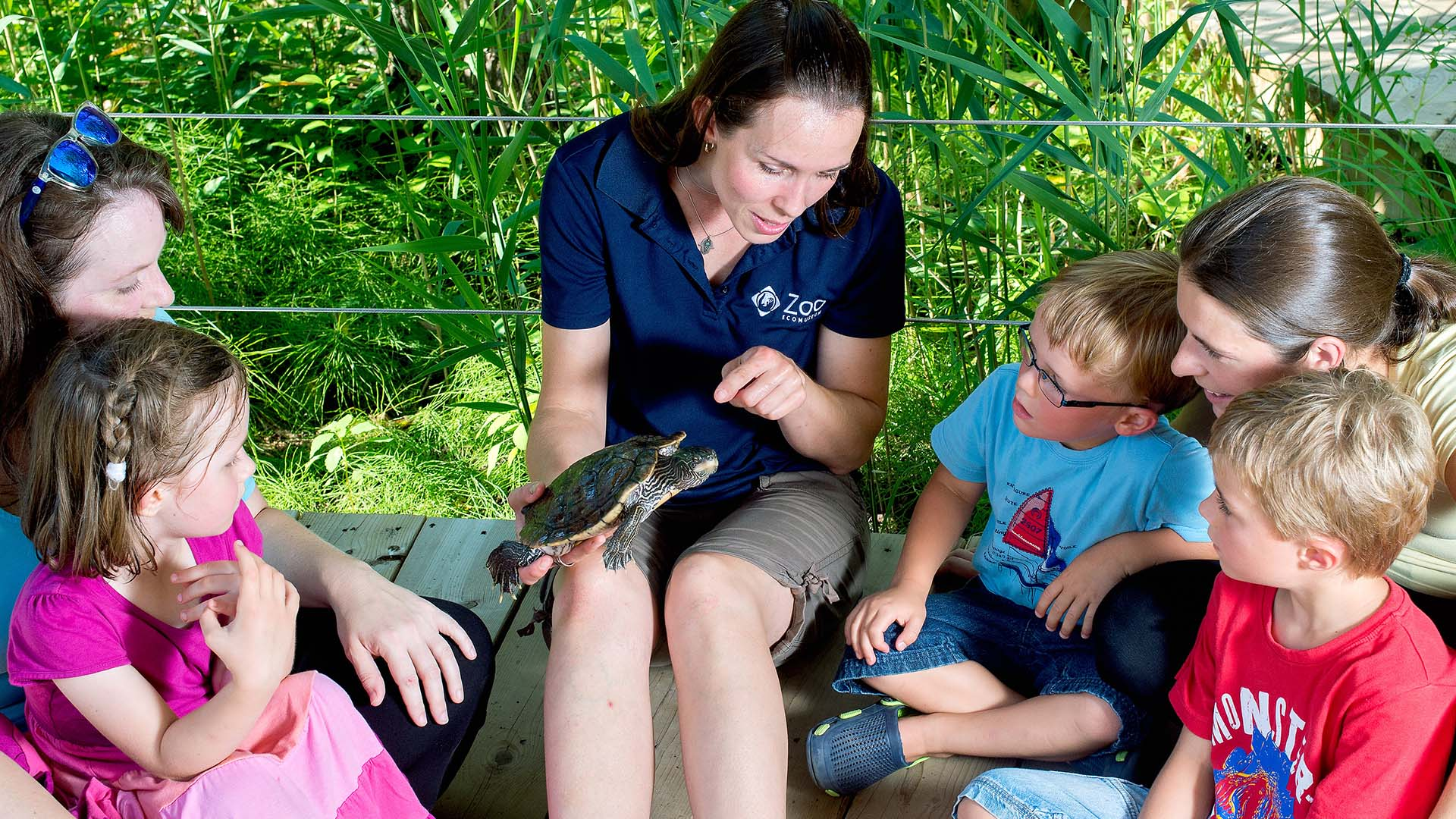 kids and parents sitting around a zookeeper holding a turtle during the Zookeeper-for-a-day activity at the Zoo Ecomuseum